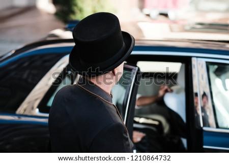 Hotel doorman opens luxury car door for a young woman
