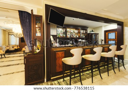 Hotel lounge bar with bottle shelves and seats. Barroom in restaurant, ready for work, copy space. Cafe background #776538115