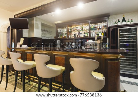 Hotel lounge bar with bottle shelves and seats. Barroom in restaurant, ready for work, copy space. Cafe background #776538136
