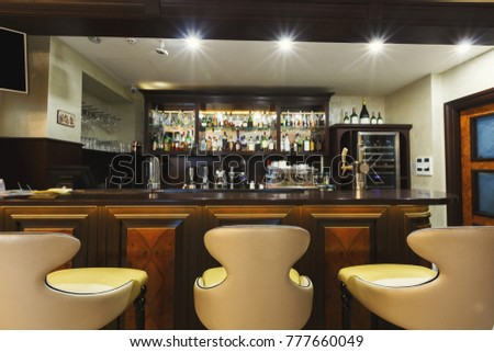 Hotel lounge bar with bottle shelves and seats. Barroom in restaurant, ready for work, copy space. Cafe background #777660049