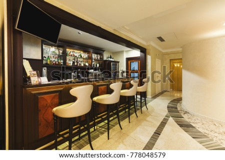 Hotel lounge bar with bottle shelves and seats. Barroom in restaurant, ready for work, copy space. Cafe background #778048579