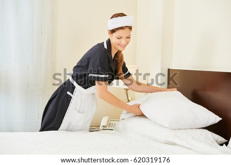 Hotel maid making bed in hotel room during house keeping