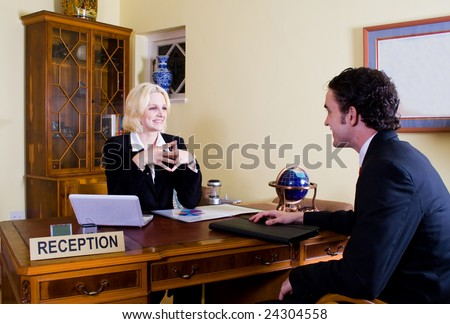 hotel manager at reception with customer
