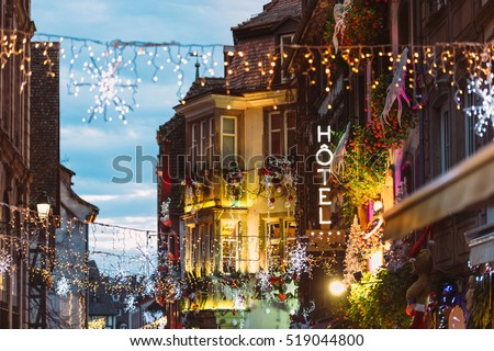Hotel neon sign on romantic luxury building above colorful Christmas Market atmosphere with people silhouettes Christmas toys and decorations in oldest Christmas Market worldwide, Strasbourg
