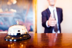 Hotel reception bell and receptionist greeting handshake