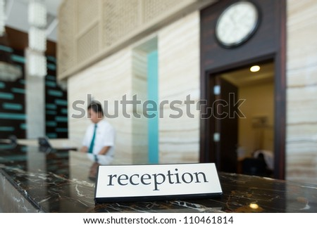 Hotel reception desk with a table and receptionists on a background