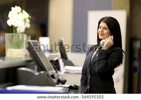 Hotel receptionist. Modern luxury hotel reception counter desk with bell. Happy female receptionist worker standing at hotel counter. #564595501