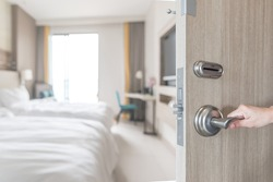 Hotel room door opened unlock to guest bedroom interior view with blur background of modern comfort bed luxury high quality living space for traveller