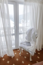 Hotel room in a mountain resort in winter with a white robe and a tablet on a chair, showing a nice bright view from the apartment through a window.