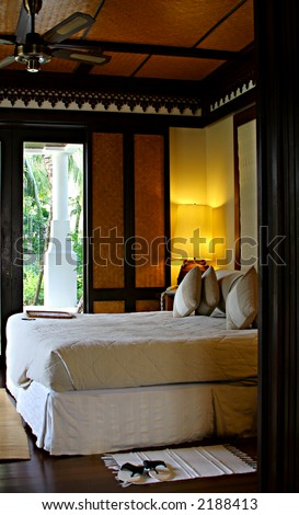 Hotel room in a tropical resort with a comfortable bead and wooden flooring. Concept: Travel and vacation.