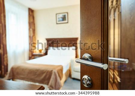 Hotel room or apartment doorway with open door and bedroom in background