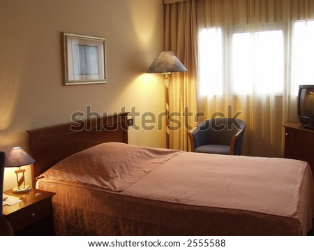 Hotel room showing the bed night stand and lamp