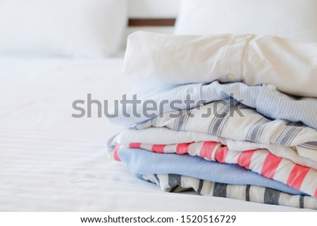 Hotel room with freshly made bed, perfectly clean and ironed sheets, stack of new dry cleaned folded set of clothing in natural sun light. Close up, copy space for text. #1520516729