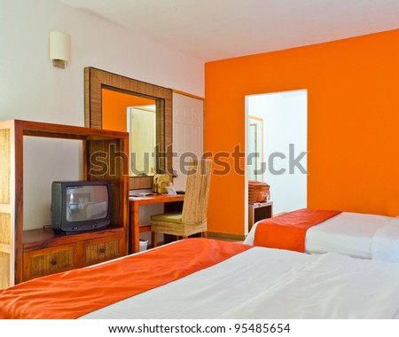 hotel room with orange wall and blanket on the bed.