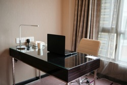 Hotel room work desk with black laptop, white cup, table lamp and telephone