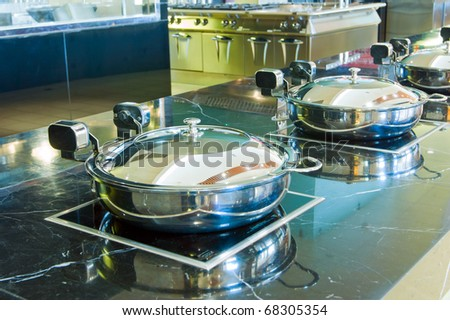 Hotel's kitchen, stainless steel pot close-up.