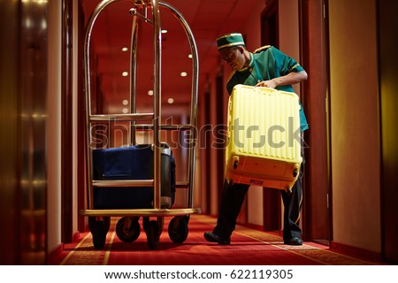 Hotel servant taking out suitcase with baggage from hotel room #622119305