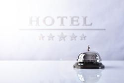 Hotel service bell on a table white glass and placard hotel and stars background. Concept hotel, travel, room