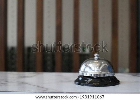 Hotel service bell on a table white glass and simulation hotel background. Concept hotel, travel, room , A service bell in a hotel