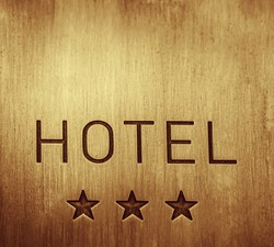 HOTEL  signboard with  three 3 stars metallic plate next to entrance door. 3 three  golden stars. empty copy space for inscription.