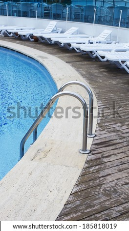 Hotel swimming pool. Grab bars ladder in the blue swimming pool. Sunbeds