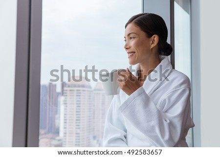 Hotel woman drinking morning coffee relaxing wearing bathrobe looking at view from bedroom window or spa. Luxury living resort lifestyle Asian travel guest enjoying room service.