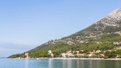 Hotels seen at the foot of the steep sides of the Peljesac mountains in Orebic, Croatia.