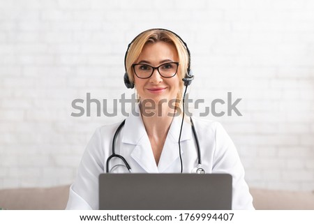 Hotline in hospital. Smiling female doctor in white coat, in headphone with laptop on white brick wall background