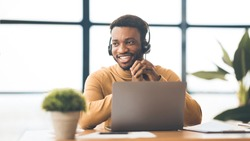 Hotline Support Service. Black operator in headset working in call center, panorama, copyspace