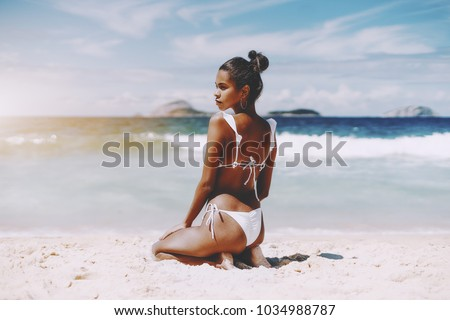 Hottie young African American female model is sittingon the sand half-turned to camera in front of ocean; rear view of foxy Brazilian girlsitting on the beach of warm summer sea with horizon behind