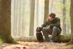 Hound as a hunting dog together with a hunter or forester take a break in the forest