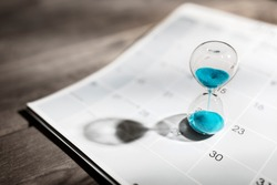 Hour glass on calendar concept for time slipping away for important appointment date, schedule and deadline