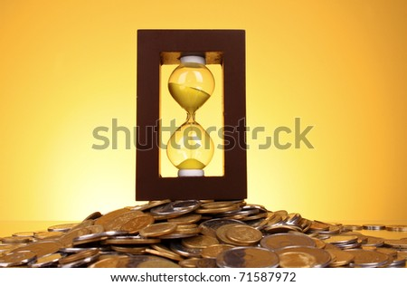 Hourglass and coins on yellow background