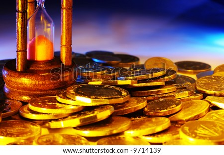 Hourglass and coins, with warm gold and blue lighting.  Time is money.