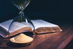 Hourglass and open bible symbolizing the end times according to the Holy Bible. Time is running out.