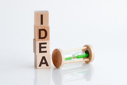 hourglass and wooden blocks with the word Idea. The concept of financial risk. Investing in a business project. Making the right decision. Property insurance. Legal market idea