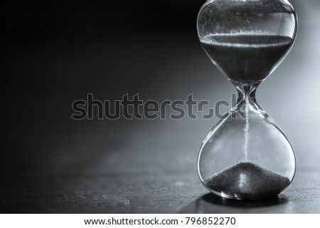 Hourglass as time passing concept for business deadline, urgency and running out of time. Sandglass, egg timer on wooden floor showing the last second or last minute or time out.  With copy space. #796852270