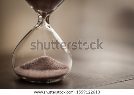 Hourglass as time passing concept for business deadline, urgency and running out of time. With blurred background and copy space. Sandglass.