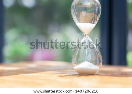Hourglass as time passing on brown wooden background. Beauty and past moments concepts. Soft focus