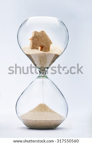 Hourglass house mortgage concept. House flowing down in the hourglass