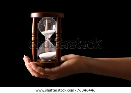 Hourglass in hands on a black