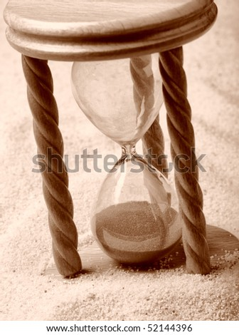 Hourglass in sand, shallow depth of field