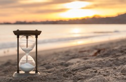 Hourglass in the dawn time. Sand passing through the glass bulbs of an hourglass measuring the passing time as it counts down to a deadline or closure on a sunset/ sunrise beach background.