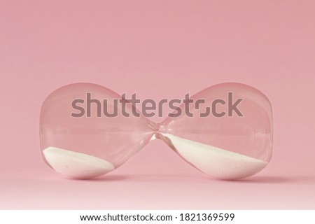 Hourglass lying on pink background - Concept of time and woman