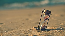 Hourglass on a sand dune beach. (vintage style)