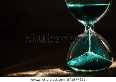 Hourglass on dark background with long shadow. #571679623