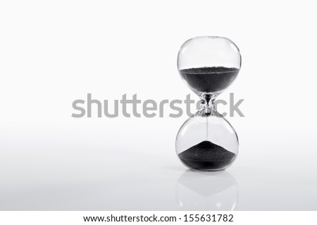 Hourglass on gradient white background with Black Sand.