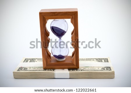 Hourglass on pile of paper money over  white background