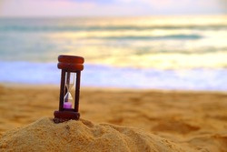 hourglass on sand beach means time is passing by day