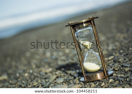 Hourglass on stony beach, photographed at an angle.